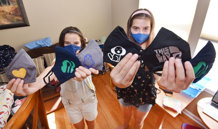 Sisters Jaina, 10, and Olivia Bartusch, 11, are decorating and selling face masks.