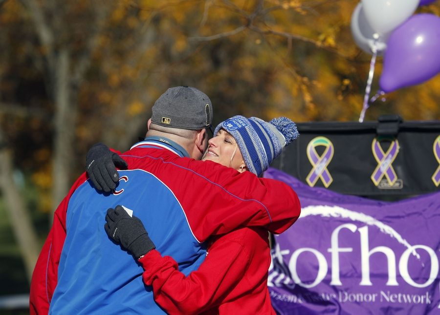 Marisa Marton gets a hug from Clay Bennett of Elgin on Friday before the start of the Andrew Marton Memorial Golf Outing at Palatine Hills Golf Course & Clubhouse in Palatine.