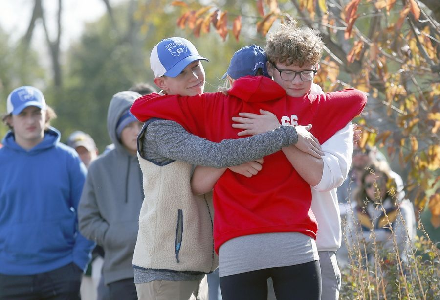 Marisa Marton gets a hug from her son's friends Nate Elliott, left, and Malik Krech before the start of the Andrew Marton Memorial Golf Outing on Friday at Palatine Hills Golf Course & Clubhouse in Palatine.