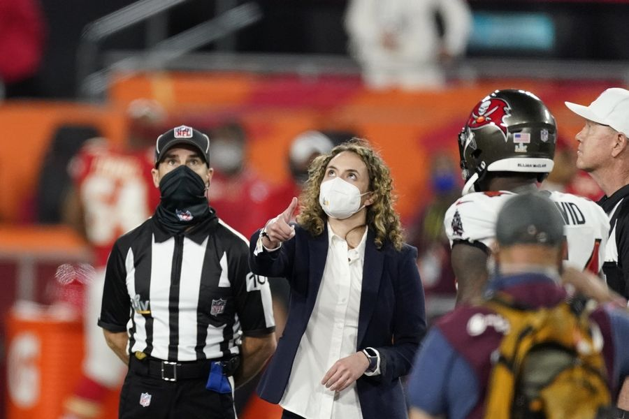 A health care worker tosses the coin before the NFL Super Bowl 55 football game between the Tampa Bay Buccaneers and the Kansas City Chiefs, Sunday, Feb. 7, 2021, in Tampa, Fla.