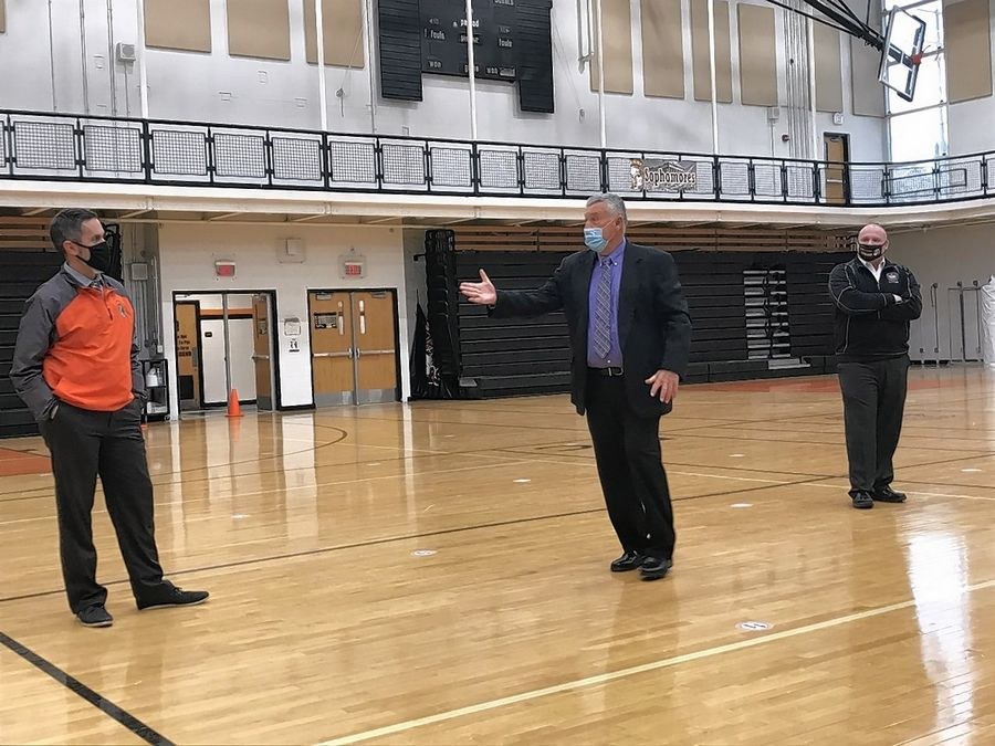 McHenry East High School Principal Jeff Prickett, left, is surprised by Illinois Principals Association representative Frank Conroy, center, and District 156 Superintendent Ryan McTague, right, during an announcement that Prickett is the 2021 IPA high-school principal of the year.