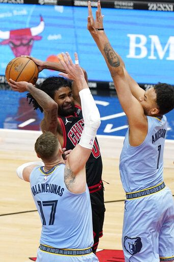 Chicago Bulls guard Coby White, center, drives to the basket as Memphis Grizzlies center Jonas Valanciunas (17) and forward Kyle Anderson guard during the second half of an NBA basketball game in Chicago, Friday, April 16, 2021.