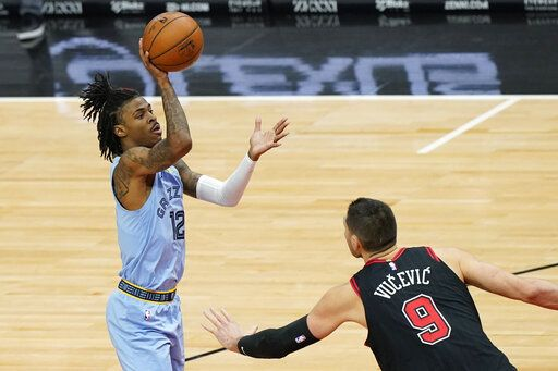 Memphis Grizzlies guard Ja Morant, left, shoots as Chicago Bulls center Nikola Vucevic defends during the first half of an NBA basketball game in Chicago, Friday, April 16, 2021.