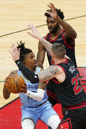 Memphis Grizzlies guard Ja Morant, left, looks to pass the ball as Chicago Bulls center Daniel Theis, right, and forward Patrick Williams defend during the first half of an NBA basketball game in Chicago, Friday, April 16, 2021.