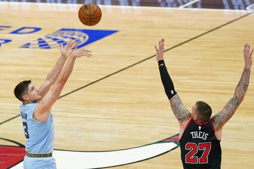 Memphis Grizzlies guard Grayson Allen, left, shoots against Chicago Bulls center Daniel Theis during the first half of an NBA basketball game in Chicago, Friday, April 16, 2021.