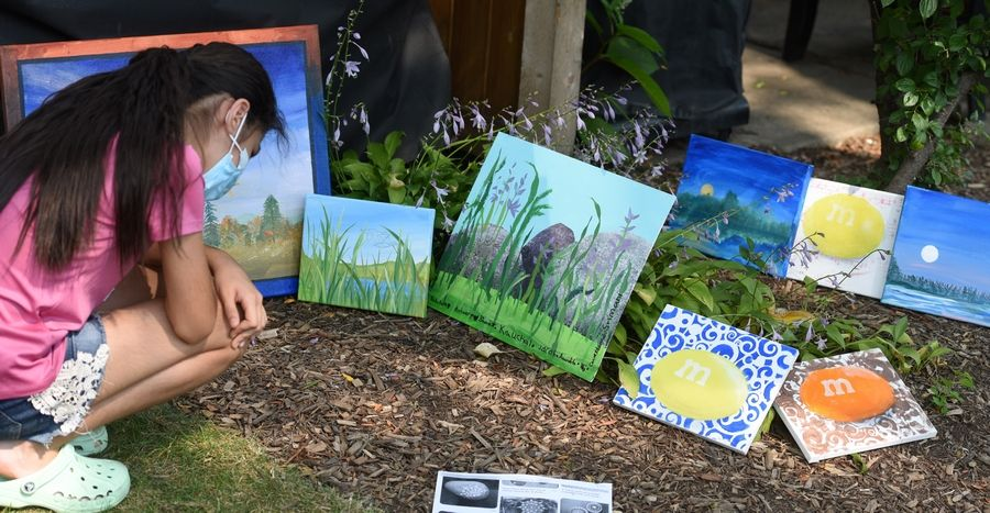 11-year-old Manal Sultanova sees some of the paintings she and her neighborhood friends painted throughout the summer in sessions led by Carol Keene in her backyard in Buffalo Grove.